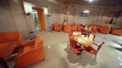 Chairs and tables in empty cafe-bar in orange tones Stock Footage