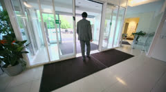 Man walks through entrance glass door of office building - stock footage