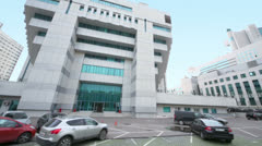 Cars parked near modern office building, (panoramic motion) Stock Footage
