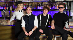 Four young members of rock band sit near bar counter. Stock Footage