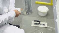 Worker in white uniform cleans spattle from putty, closeup Stock Footage