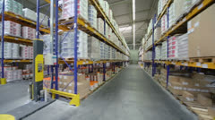 Rows of shelves with good in large warehouse at Caparol factory Stock Footage