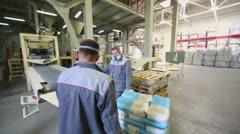 Two men work on conveyor of Caparol factory Stock Footage