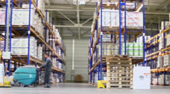 People work in warehouse with goods on shelves at factory Stock Footage