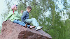 Two kids boy and girl sit on huge red stone near birch Stock Footage