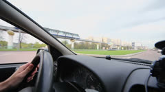 Man ride in car by street with traffic and train on monorail Stock Footage