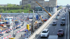 Cars ride by third transport rind near building site Stock Footage
