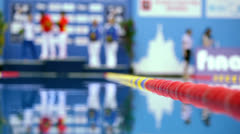Several sportsmen stand on pedestal near pool Stock Footage