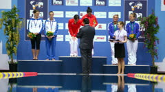 Man awards athletes on pedestal at Pool of Sport Complex Olympic Stock Footage