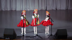 Three girls in folk costumes sing and dance on stage Stock Footage