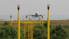 Airplane takes off over landing lights at manchester airport, england Stock Footage