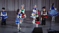 Several children in folk costumes play on tambourines and dance Stock Footage
