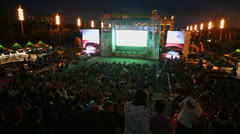 Many football fans watch game on big screen in Fanzone Stock Footage
