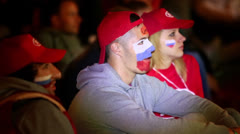 Russian fans with symbols painted on faces sit in Fanzone Stock Footage