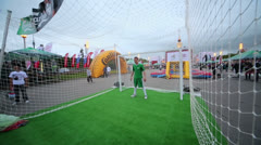 Goalkeeper stand in gate and misses ball at amusement in Fanzone Stock Footage