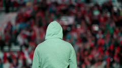 Football fan in hood stand against tribunes with crowd Stock Footage