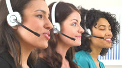 Three customer service representatives talking on headsets Stock Footage