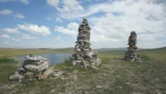 Khakassia. Stone cairns on top of the hill (pan up) Stock Footage