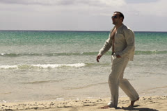 Man walking on the beach, slow motion shot at 60fps Stock Footage