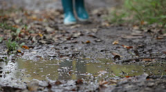 Rain boots walking in mud puddle and dirt in fall Stock Footage