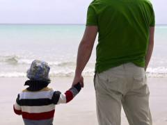 Little boy with his father standing on the beach Stock Footage