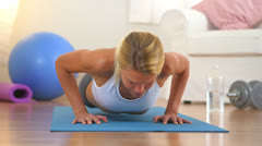 Healthy blonde woman doing push ups Stock Footage