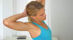 Fit blonde woman stretching at home Stock Footage