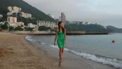 Woman walking beach, Repulse Bay, Hong Kong Stock Footage