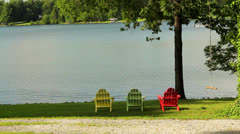 Three colorful chairs and rope swing at lake Stock Footage
