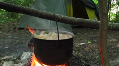 Boiling tourist soup against tent - stock footage