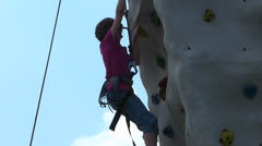Girl climbing rock wall in extreme sport Stock Footage