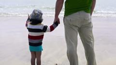Little boy with his father standing on the beach and looking at the sea Stock Footage