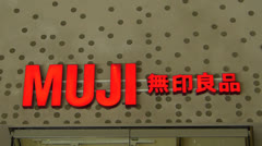 Consumer passing Japanese Brand name MUJI sign Stock Footage
