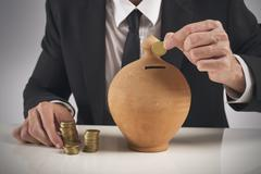 businessman saving money in a piggy bank - stock photo
