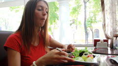 Portrait of pretty young girl with fork and bowl in hands eating vegetable salad - stock footage