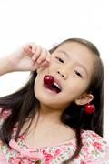 Little asian girl with fresh red cherry Stock Photos