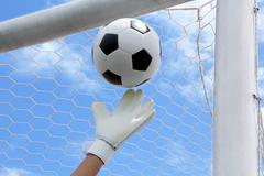 Goalkeeper's hands fail catching the soccer ball, with goal and sky in the ba Stock Photos