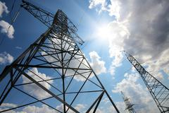 tall electric masts against sun and sky - stock photo