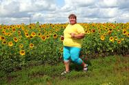 Stock Photo of overweight woman running along field of sunflowers