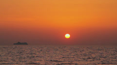 Ferryboat sailing on the horizon at sunset Stock Footage