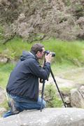 man and tripod glendalohg national park irland - stock photo