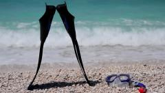Man taking his scuba diving fins, snorkel and a mask from a shingle beach Stock Footage