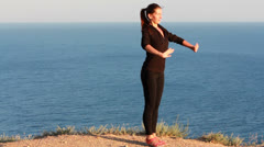 Young Woman Practicing Yoga near the Ocean Stock Footage
