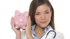 Sad doctor holding piggy bank, health care concept Stock Footage