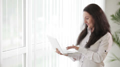 Charming young woman standing in front of window using laptop and smiling Stock Footage