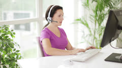 Cheerful call centre operator in headset at work using laptop - stock footage