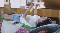 Beautiful casual young woman, laying across the back of her sofa Stock Footage