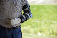 Man arm in steel prosthetic brace after surgery Stock Photos