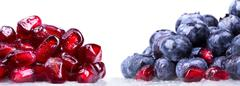 Ripe pomegranate and blue berrie background - stock photo