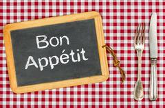 Blackboard with the text bon appetit on a checkered tablecloth Stock Photos
